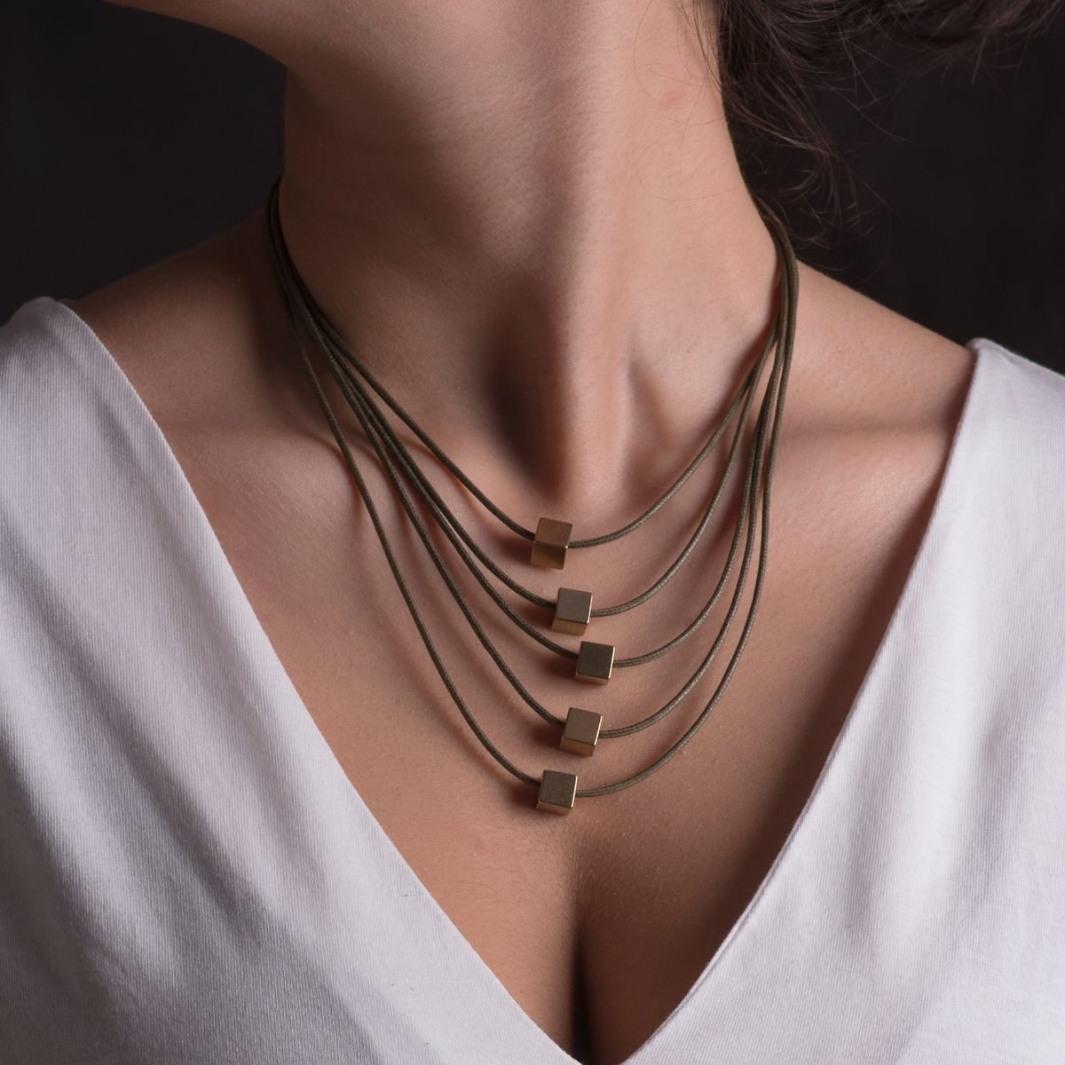 Las Vegas short necklace formed by five cotton strips at different heights in which a small cube finished in gold hangs on each of them