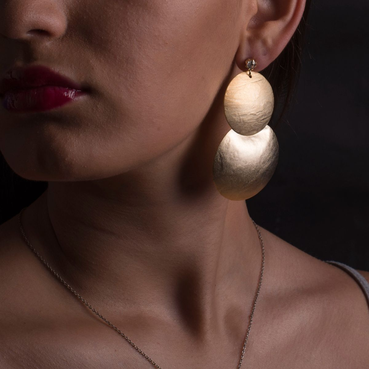 Hecate long earring with two overlapping half spheres finished in matte gold and with zirconia snap closure
